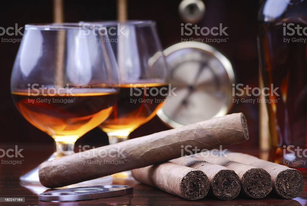 Two glasses of Cognac and cigars on a wooden table stock photo