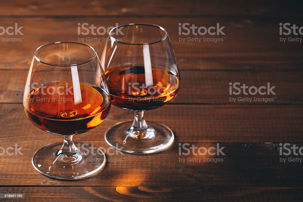 Two glasses of cognac on the wooden table. stock photo