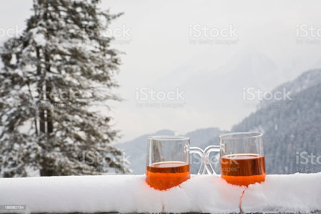 Two glasses of drink sit on a snow covered ledge  stock photo