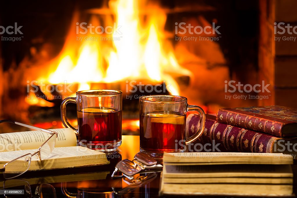 Two glasses of hot drink wine, antique books, fireplace stock photo