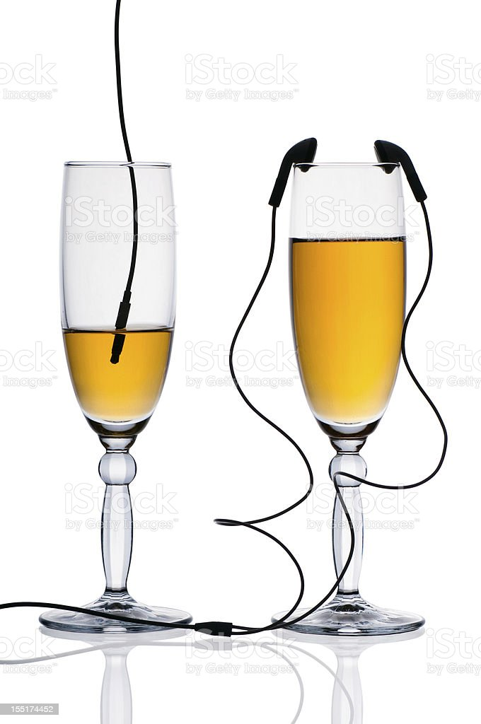 Two glasses of juice  with headphones royalty-free stock photo