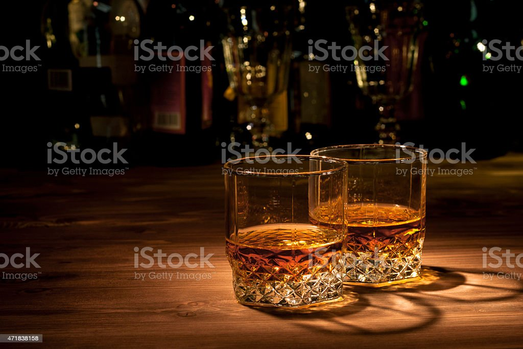 Two glasses of neat whiskey on wooden counter stock photo