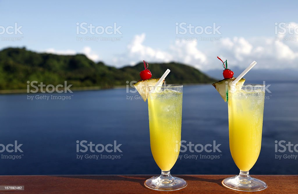 Two glasses of orange cocktail drinks by the water royalty-free stock photo