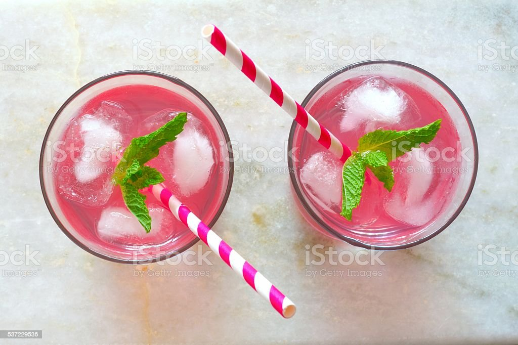 Two glasses of pink lemonade, overhead view on marble stock photo
