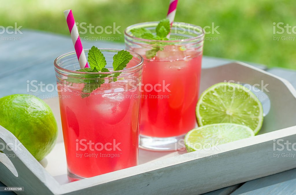 Two glasses of pink lemonade with ice and straws on a tray stock photo