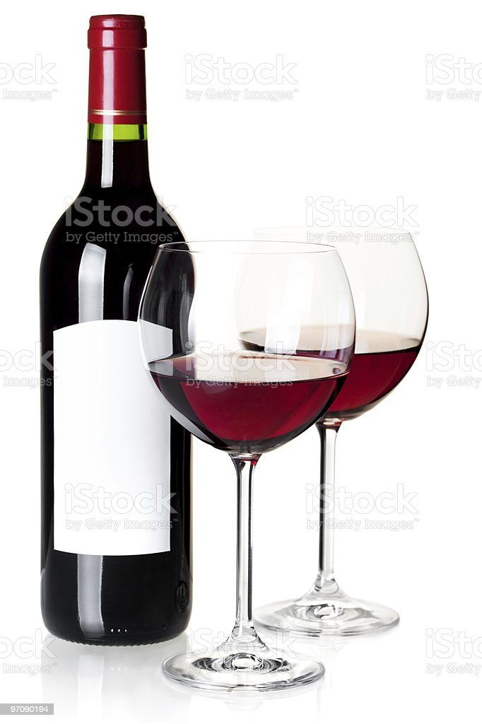 Two glasses of red wine next to a wine bottle royalty-free stock photo