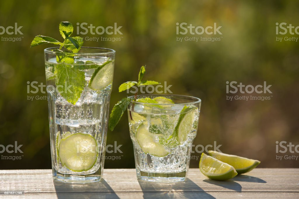two glasses of soda water on an old board, on the nature stock photo