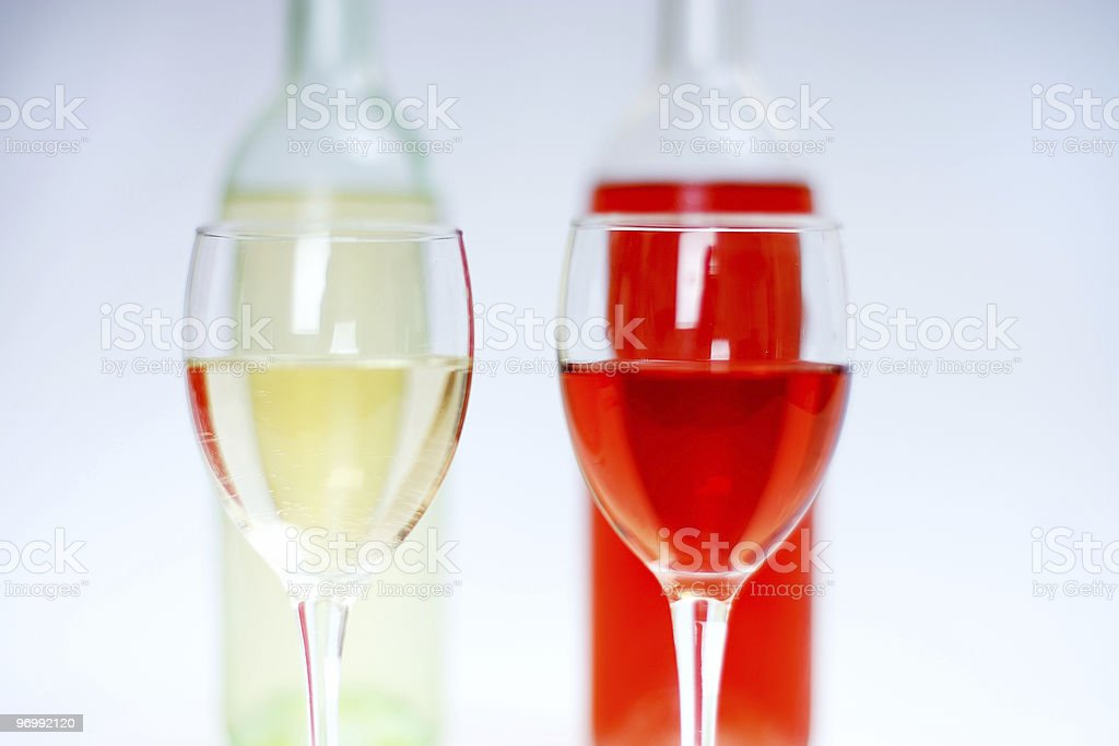 Two glasses of white and rose wine with bottles and white backgr royalty-free stock photo