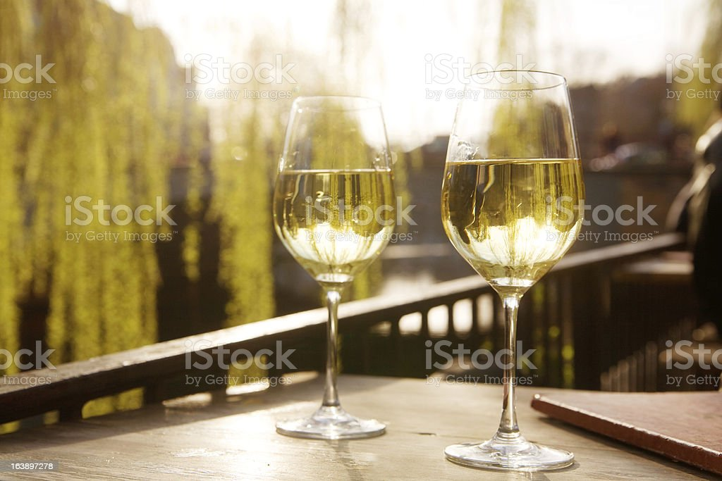 Two glasses of white wine against the sunlight stock photo