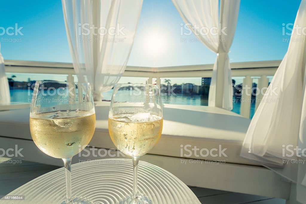 Two glasses of white wine beside a day bed. stock photo