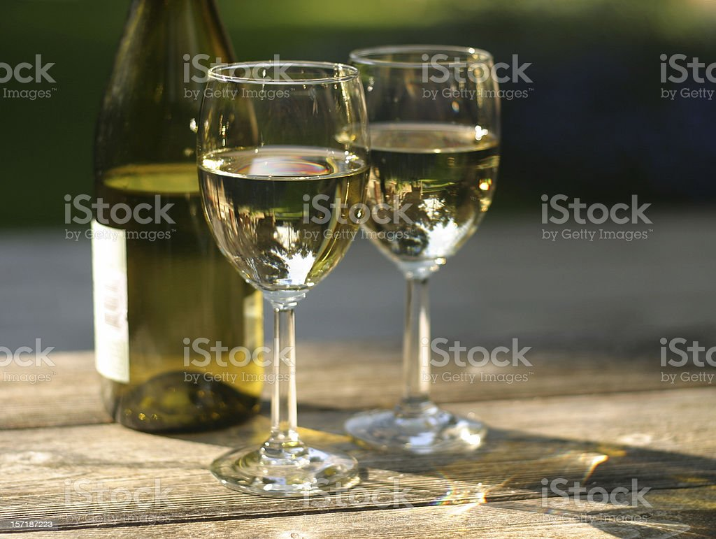 Two Glasses of White Wine with Bottle on Outdoor Table royalty-free stock photo