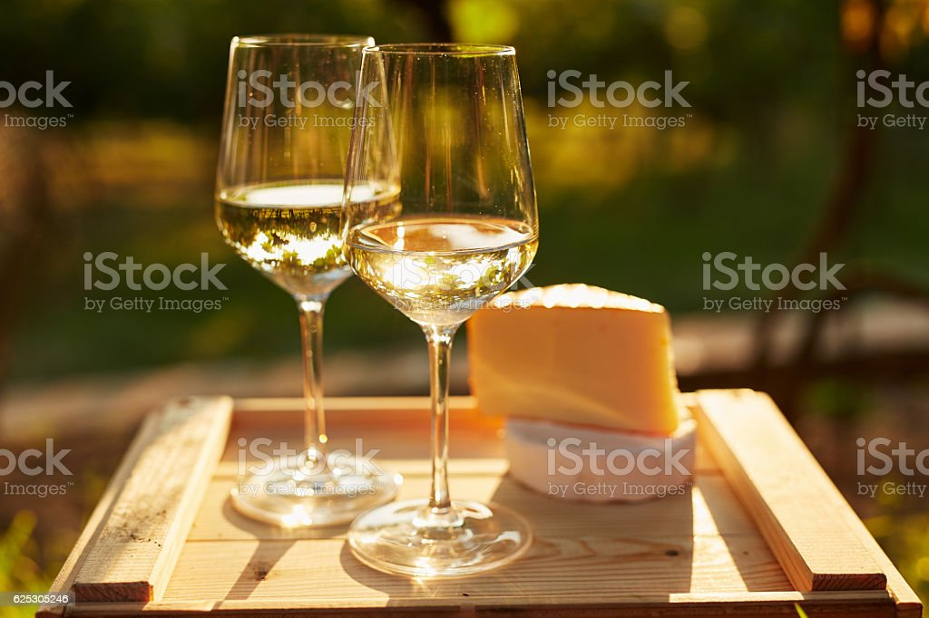 Two glasses of white wine with cheese stock photo