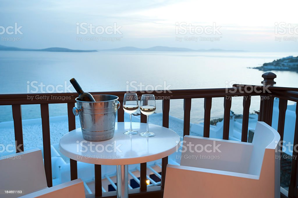 Two glasses of wine on a balcony at sunset with ocean background