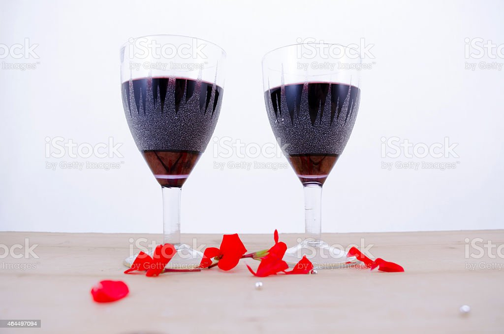 Two glasses of wine on a table with flower petals royalty-free stock photo