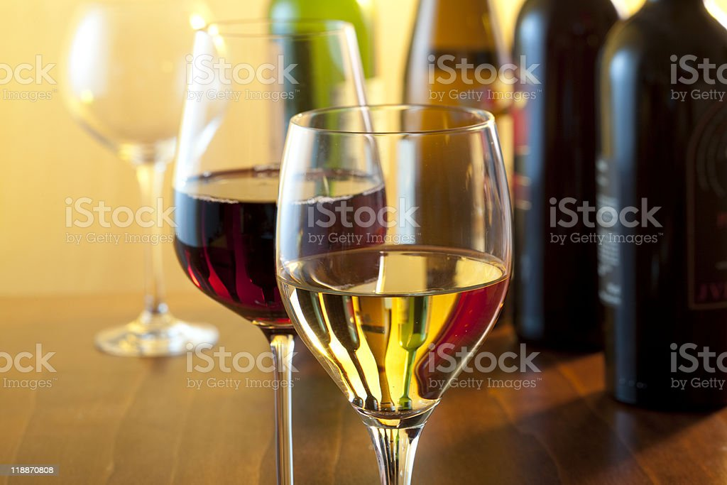 Two glasses of wine on a wooden table with wine bottles stock photo