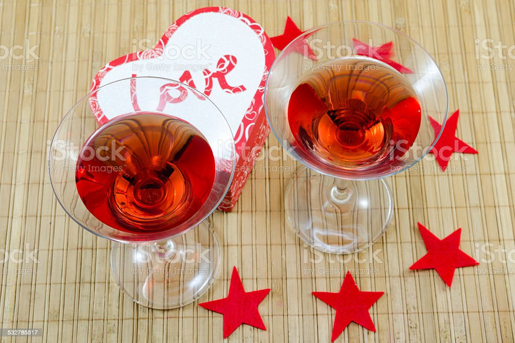 Two glasses with a red alcoholic drink and heart candles royalty-free stock photo