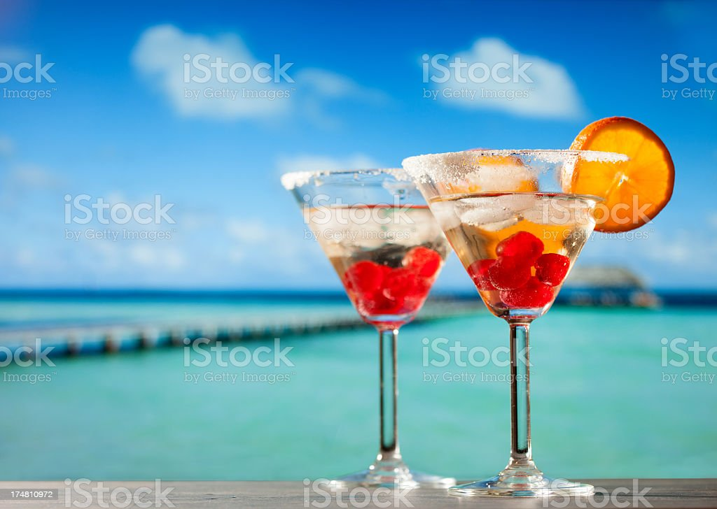Two glasses with cocktail drinks, cherries, orange on tropical beach stock photo