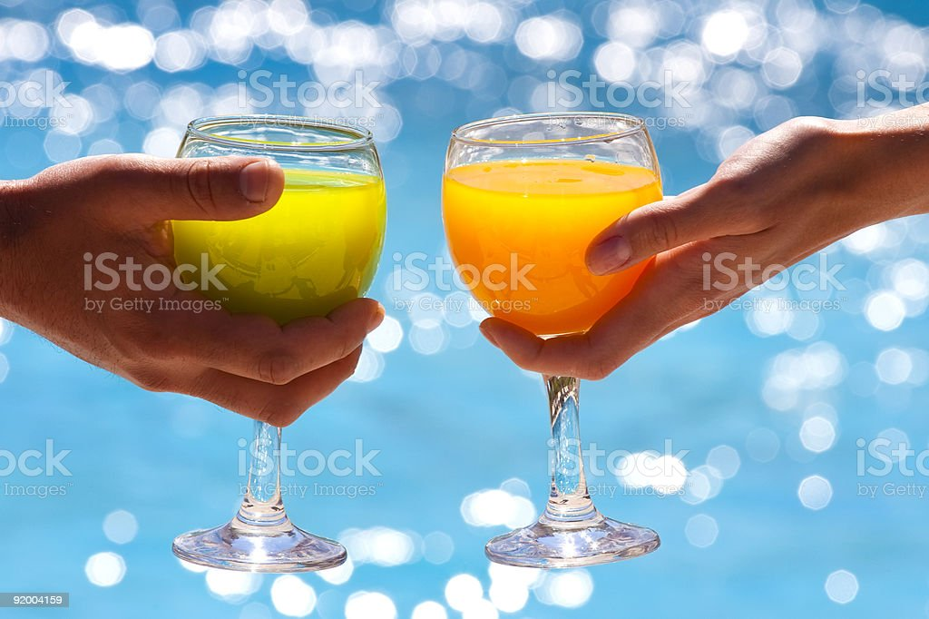 Two glasses with juice against blue water stock photo