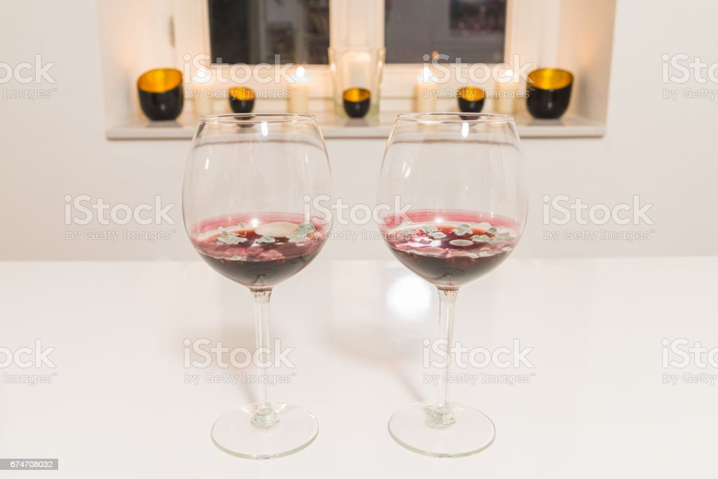 Two glasses with moldy red wine on white table with white background and window stock photo
