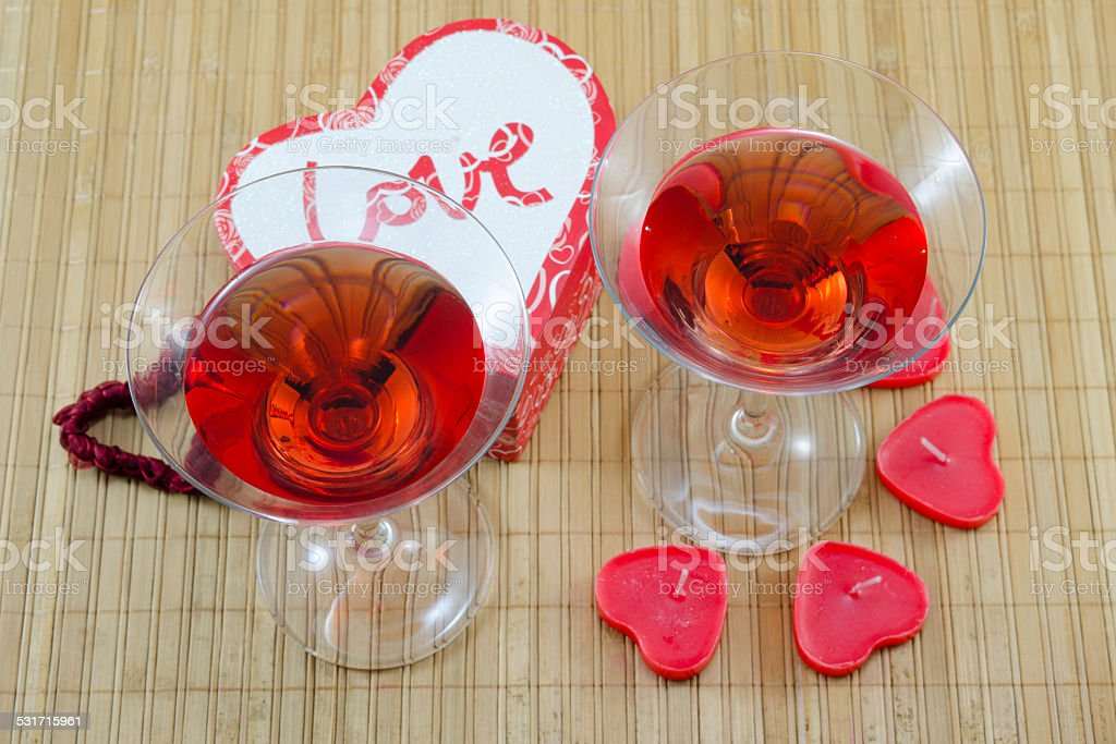 Two glasses with red alcoholic drink and heart shaped candles royalty-free stock photo