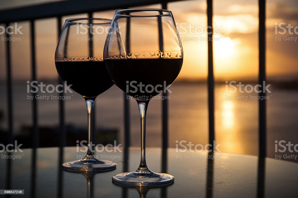 Two glasses with red wine in sunset stock photo
