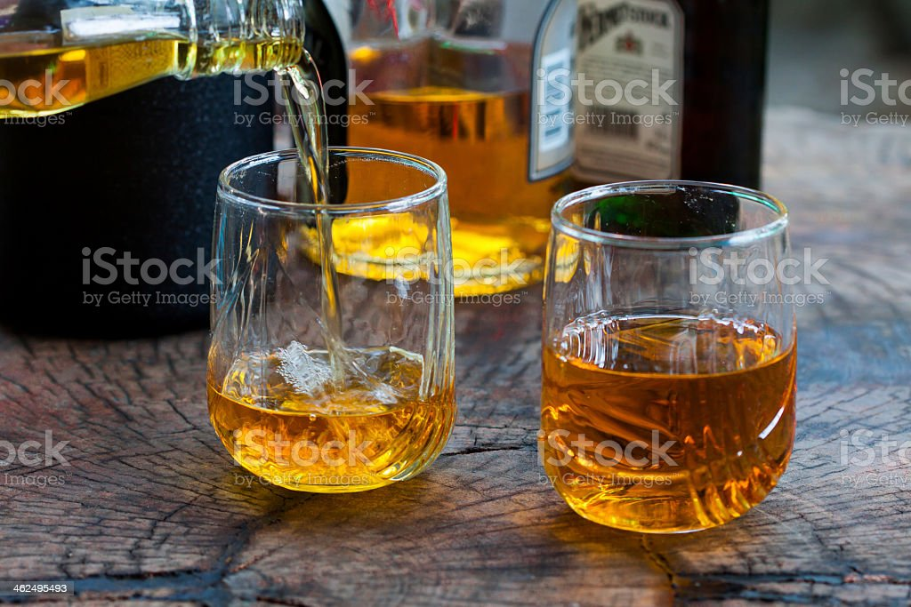 Two glasses with whiskey pouring in over a wooden table royalty-free stock photo