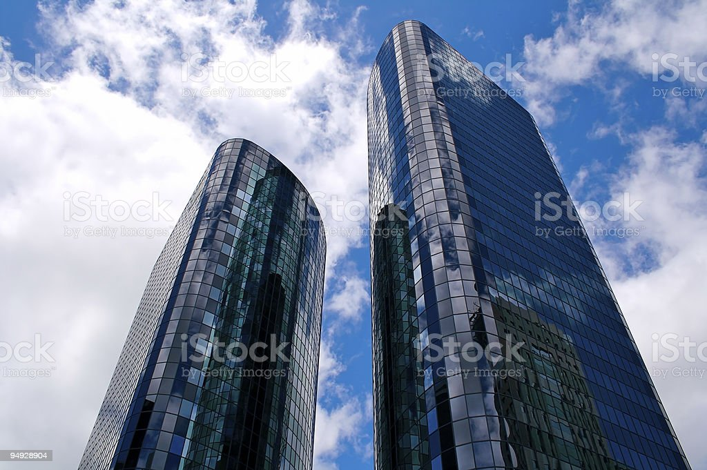 Two glass-sided towers against a cloudy sky royalty-free stock photo