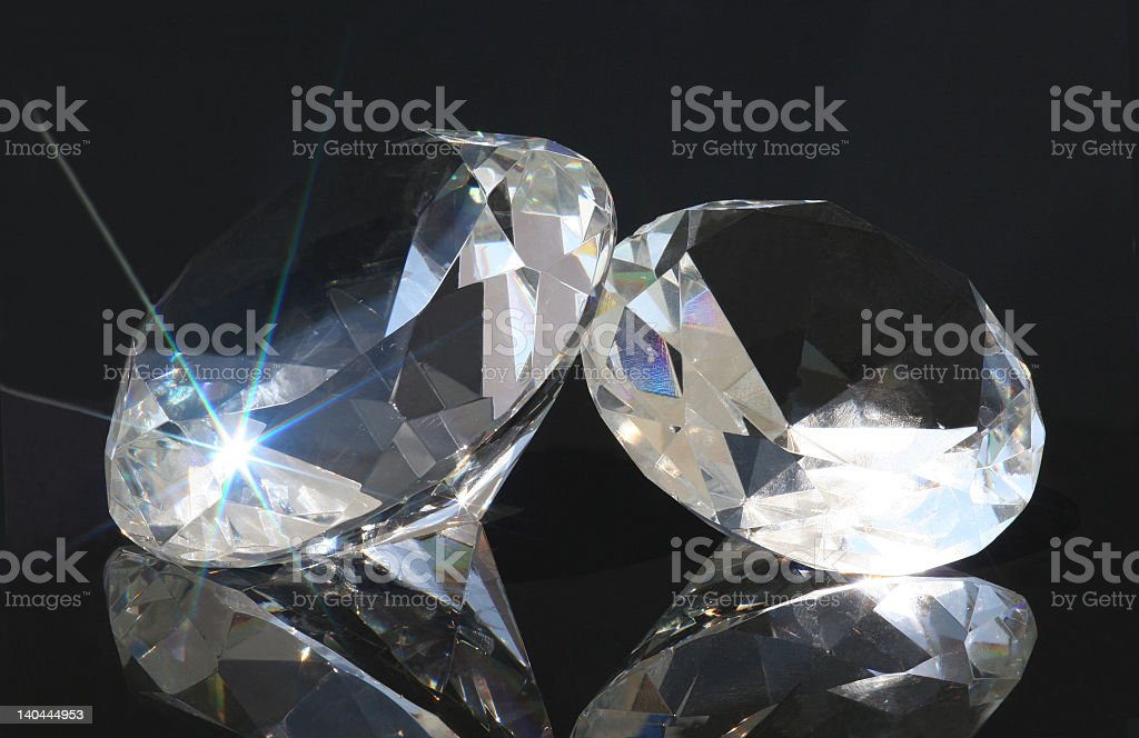Two glinting large diamonds on a black surface royalty-free stock photo