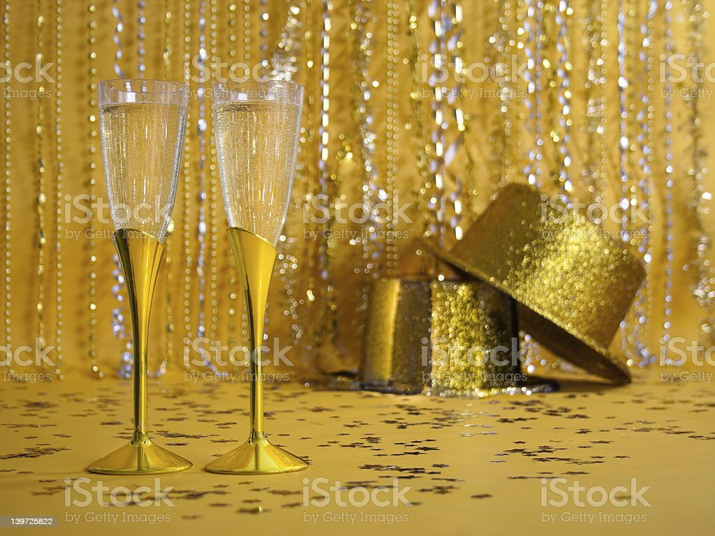 Two Gold Champagne Flutes with Sequined Party Hats stock photo