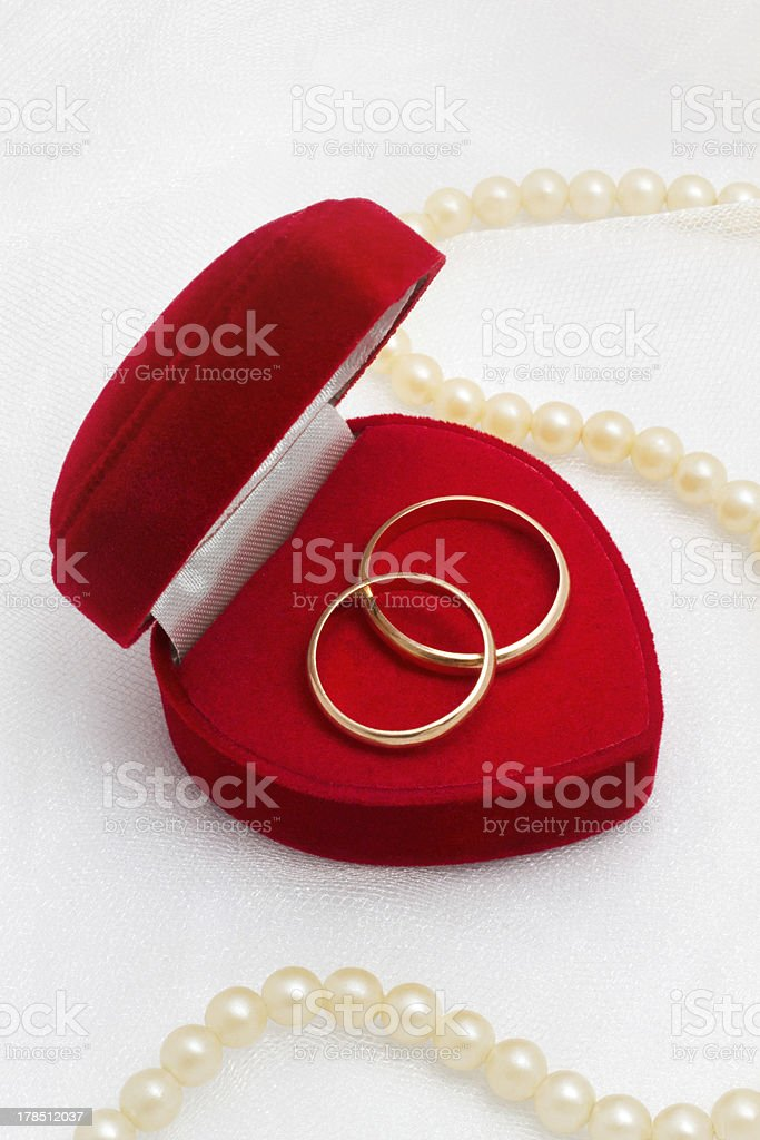 Two gold rings in red box on wedding background royalty-free stock photo