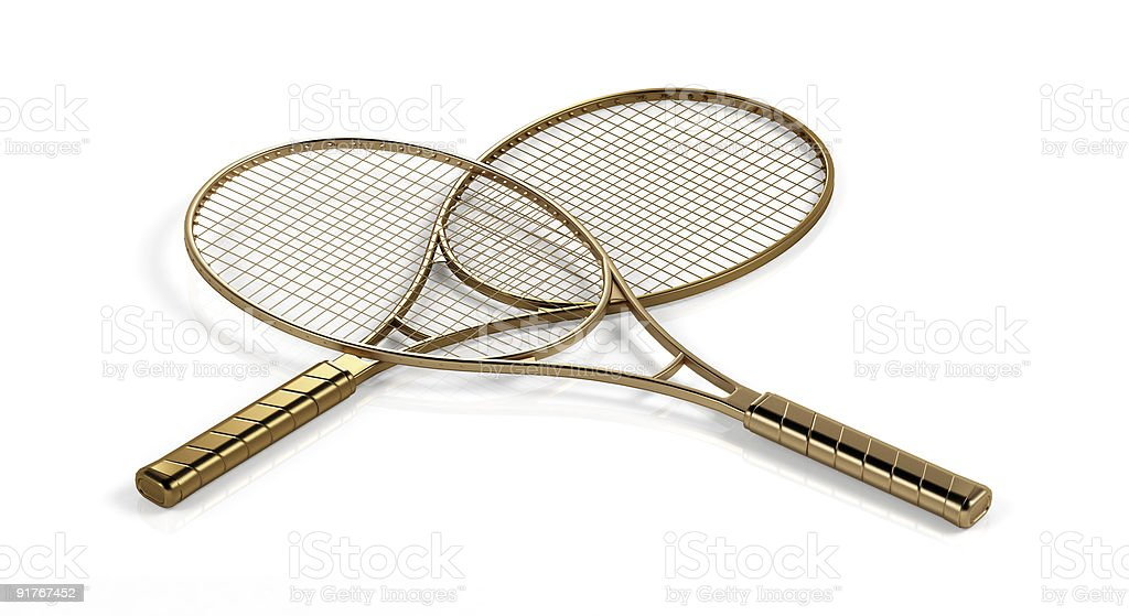 Two gold tennis rackets stock photo