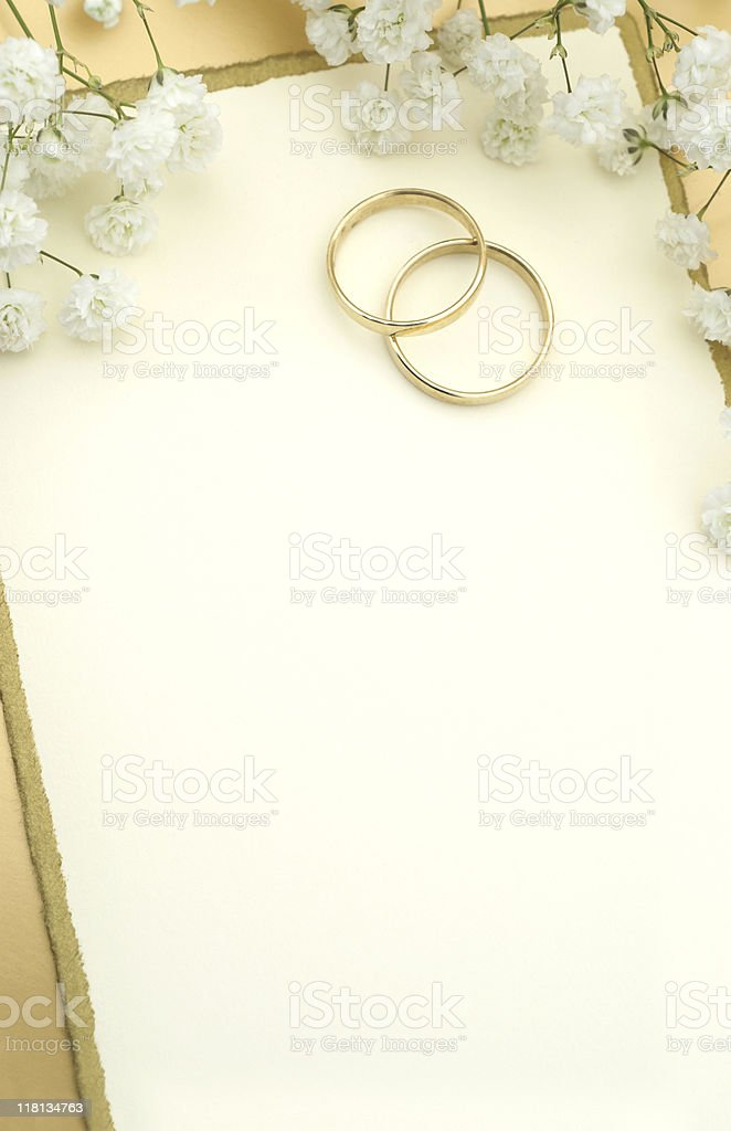 Two gold wedding bands under white flowers on white paper stock photo