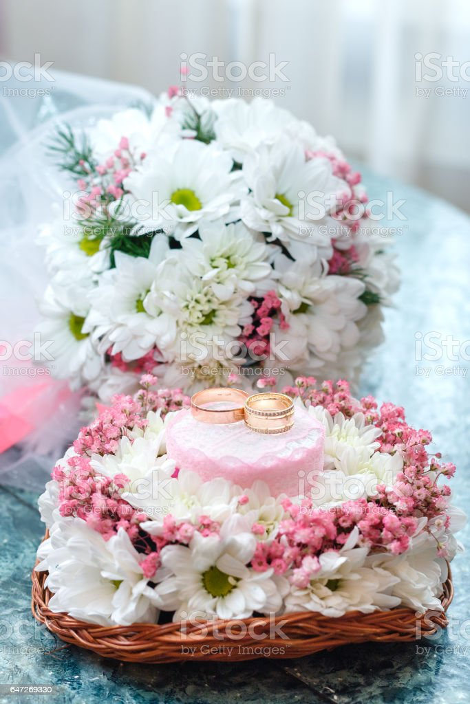 Two gold wedding rings on Beautiful white and pink bouquet in rustic basketry. stock photo