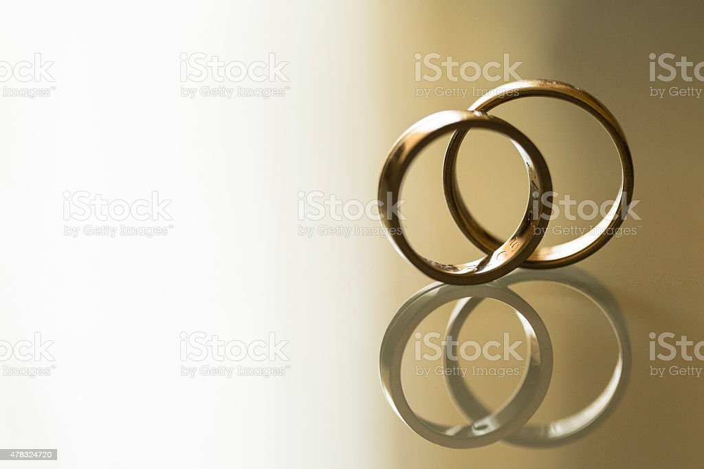 Two gold wedding rings on the glass table stock photo