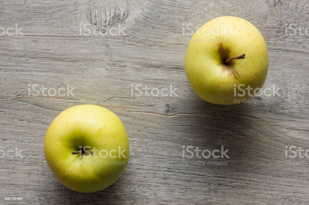 Two Golden delicious apples on wooden table stock photo