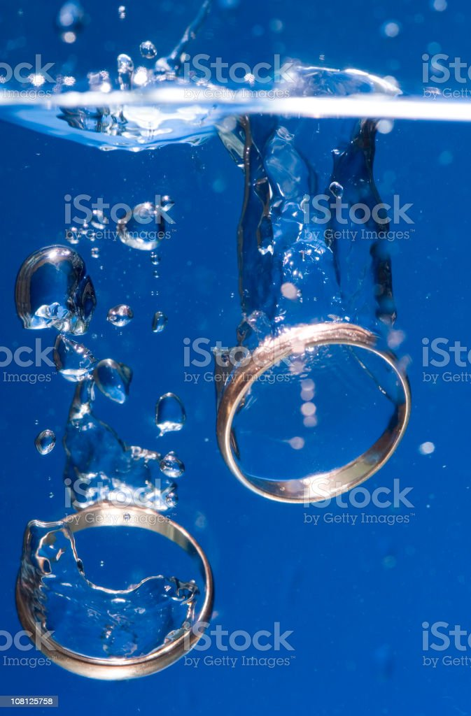 Two Golden Wedding Rings Sinking in Water royalty-free stock photo