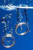 Two Golden Wedding Rings Sinking in Water