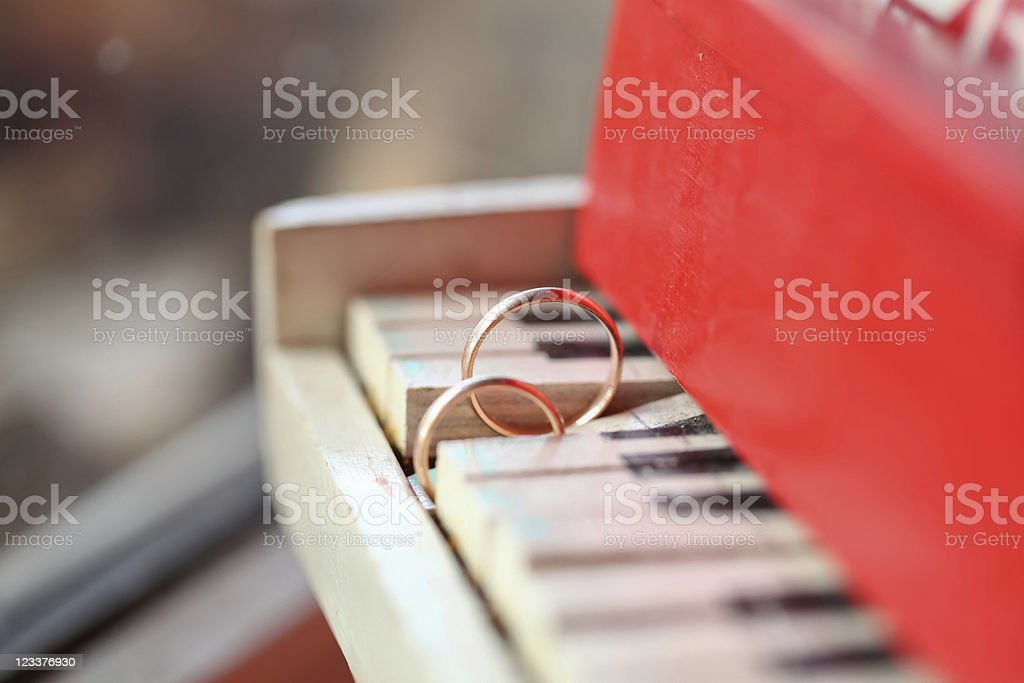 Two golgen rings on piano stock photo