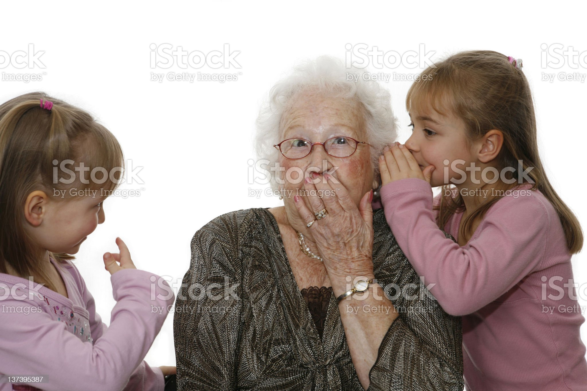 Two granddaughters sharing a secret with their grandmother royalty-free stock photo