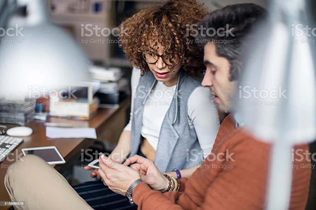 Two graphic designers reading an e-mail at the office stock photo