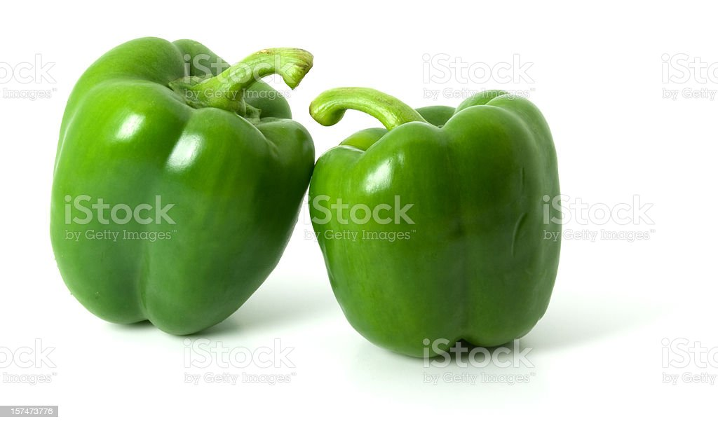 Two green bell peppers isolated on a plain white background stock photo