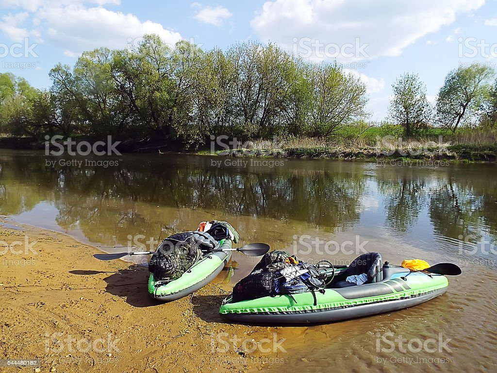two green inflatable kayaks with equipment on the river stock photo