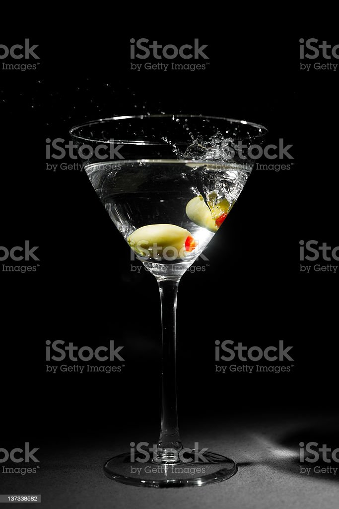 Two Green Olives Splashing into Martini Glass royalty-free stock photo