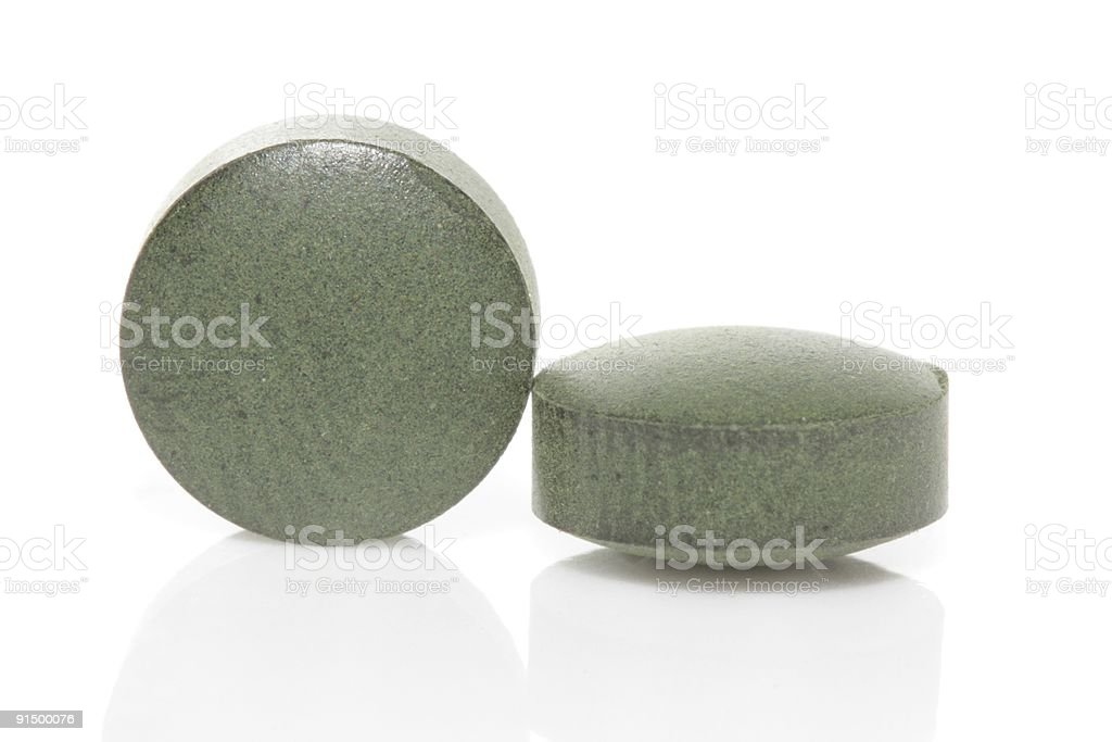 Two green spirulina tablets royalty-free stock photo