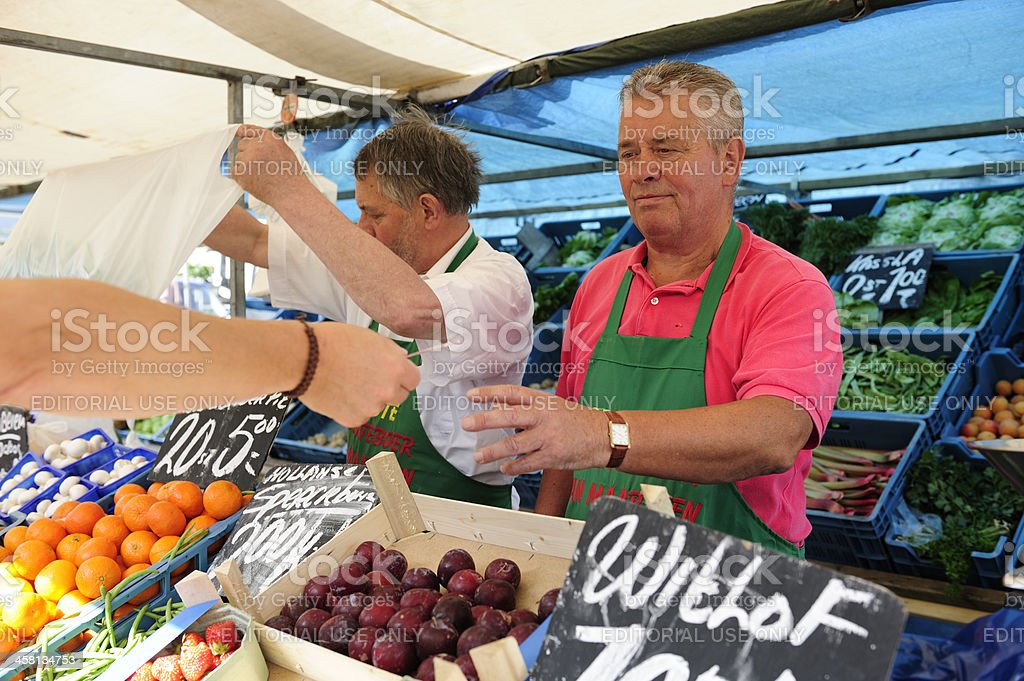 Two greengrocers at an outdoors Dutch market stall royalty-free stock photo