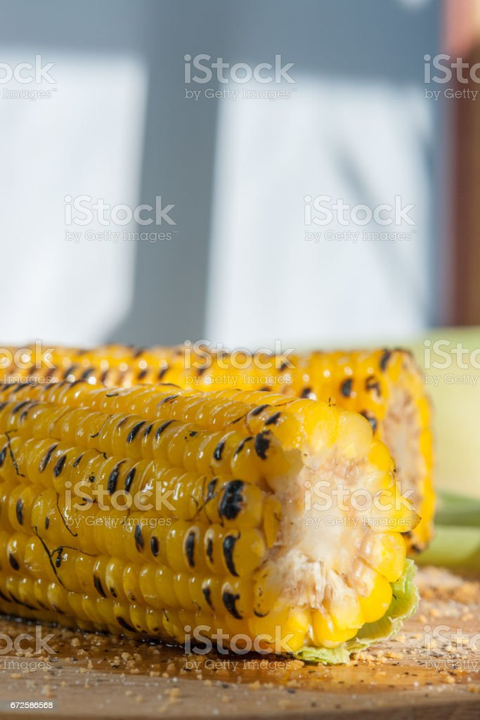 two grilled corn on a wooden plate stock photo