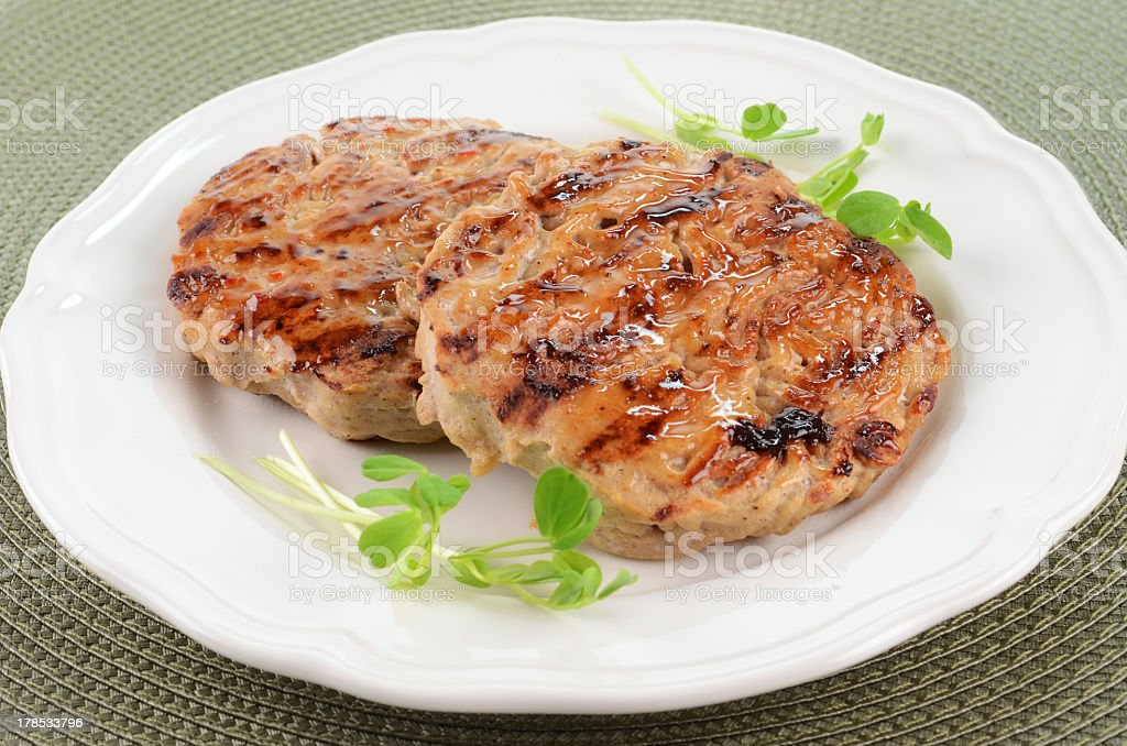 Two grilled turkey burgers served on a white plate stock photo