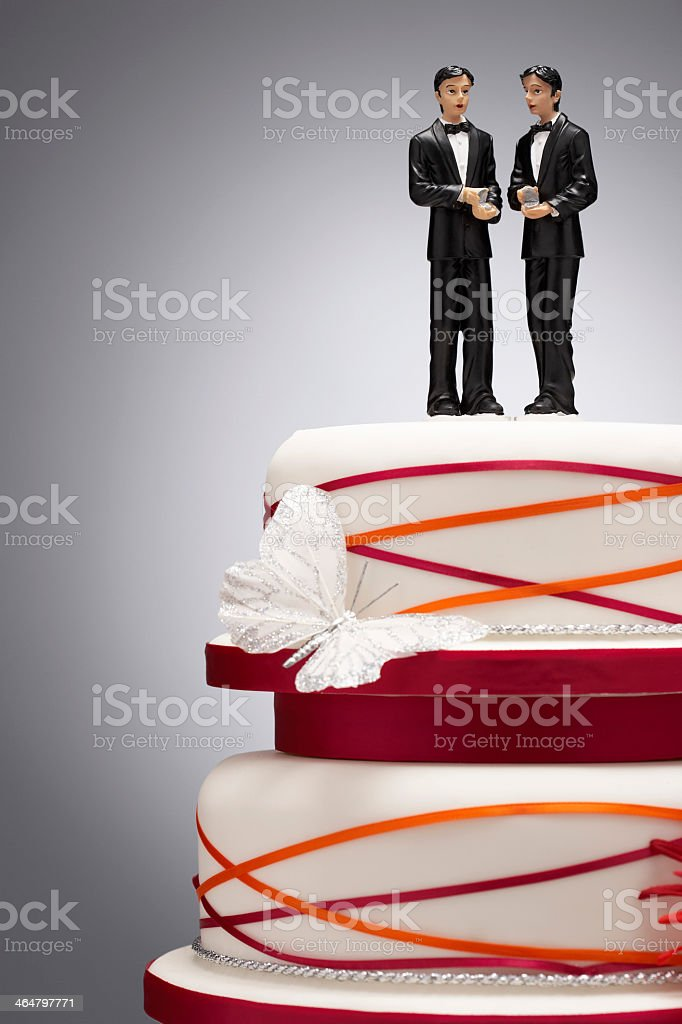 Two groom figurines on red piping wedding cake and butterfly stock photo