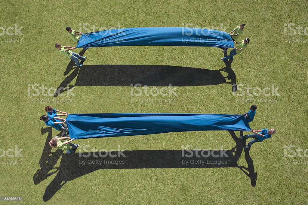Two groups of children stretching cloth between them royalty-free stock photo