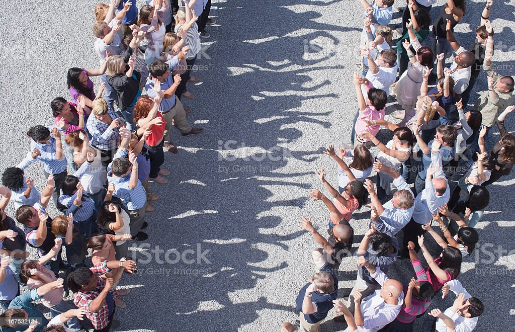 Two groups of people facing one another, arms raised royalty-free stock photo